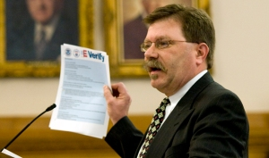SOURCE: AP/Chuck France Businessman Chris Barbee holds up a copy of instructions for the E-Verify system at the Statehouse in Topeka, Kansas. E-Verify is already in use by an estimated 4 percent of American employers, but expanding it for use by all U.S. businesses, from the mom-and-pop grocery store, to the biggest employers in the nation, presents onerous and expensive challenges.