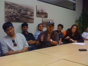 Thai worker Chakkree Sriphabun gestures, surrounded by other Thai workers and attorney Clare Hanusz
